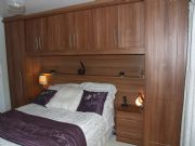 click to see larger image of Bespoke over bed unit in Walnut. Fitted in Jersey Marine, Neath Port Talbot, South Wales